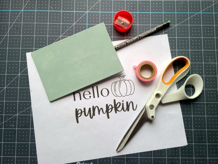 """Supplies needed for a DIY sign laid out: 4x6 canvas painted with sage chalk paint, """"hello pumpkin"""" printed on regular paper, pink washi tape, scissors, pencil, & pencil sharpener."""
