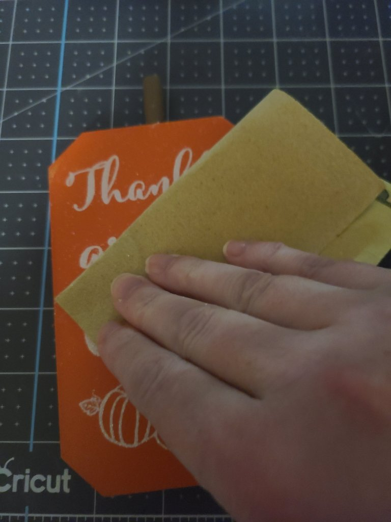 Sanding glitter off the front side of the reversible Dollar Tree pumpkins.