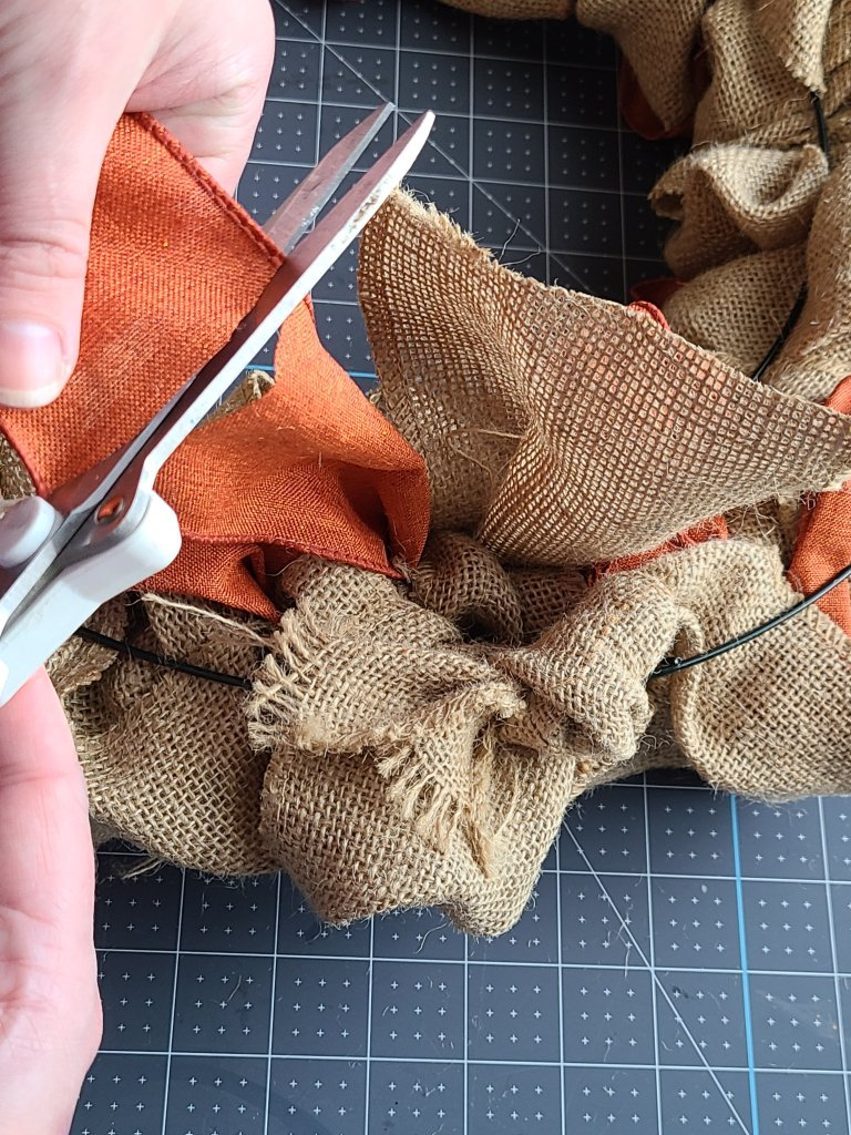 Using scissors to cut the orange ribbon from the roll.