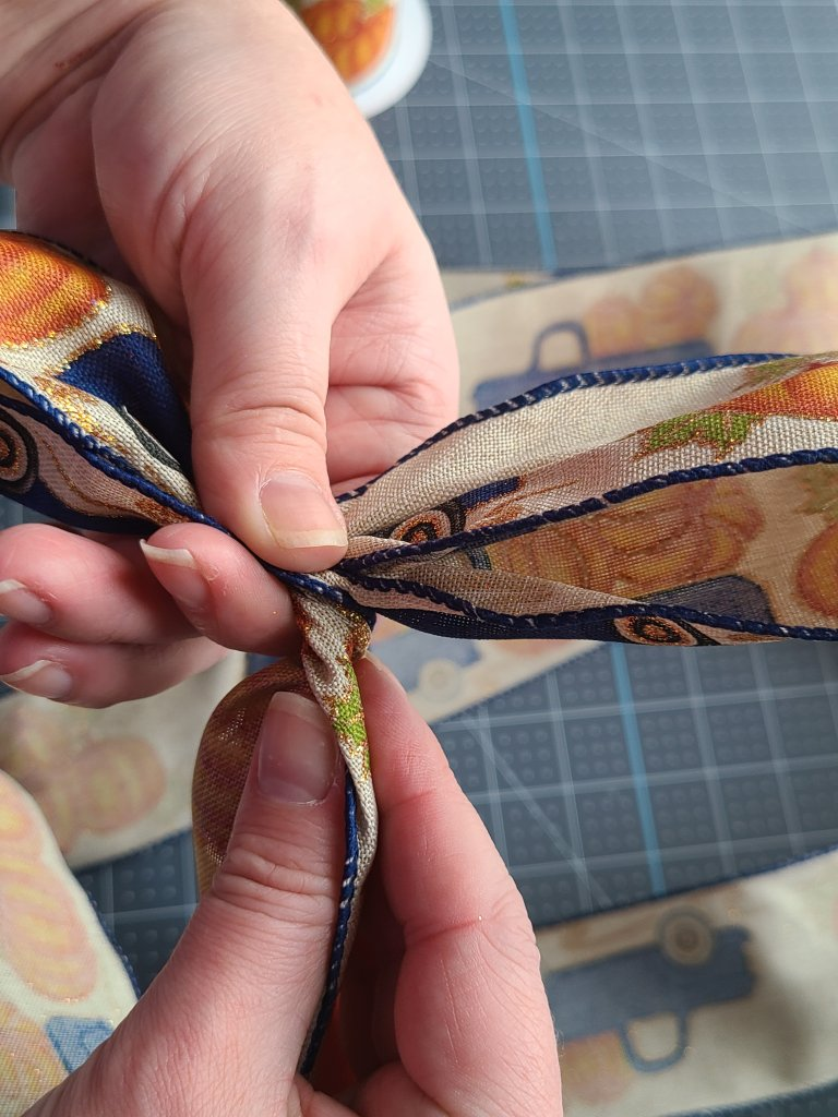 Twisting ribbon so that the print is facing up on the tutorial for making a bow for a wreath.