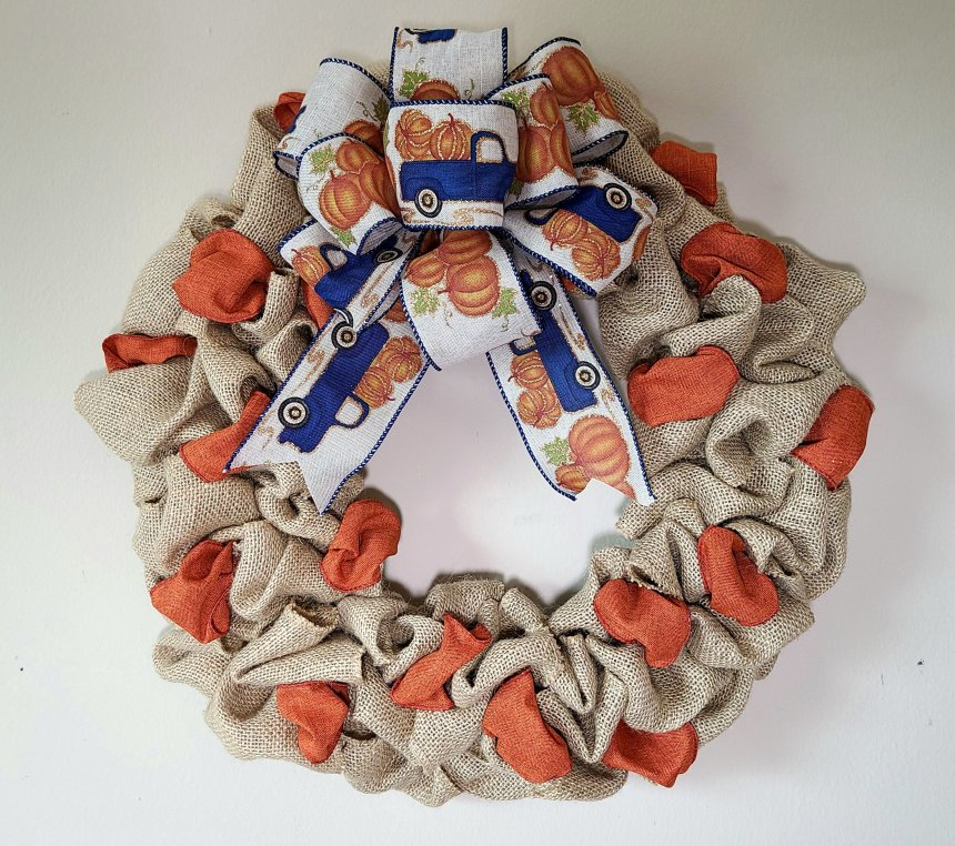 """Complete burlap wreath, 14"""" wreath with 2.5"""" wired orange ribbon running through it. A large bow made of burlap with blue side stitching & blue farmhouse trucks with pumpkins in the bed of the truck on it."""