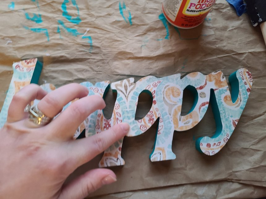 Smoothing out bubbles from the cardstock on top of of the fall Dollar Tree DIY decor word.