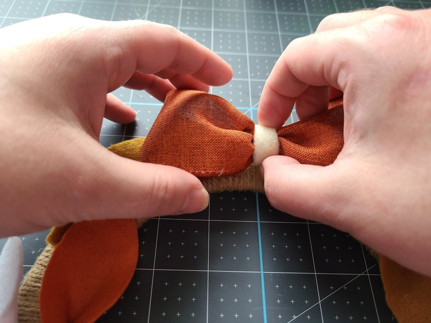 Pressing the bow with glue on the back on to the top, front of the felt leaf wreath.