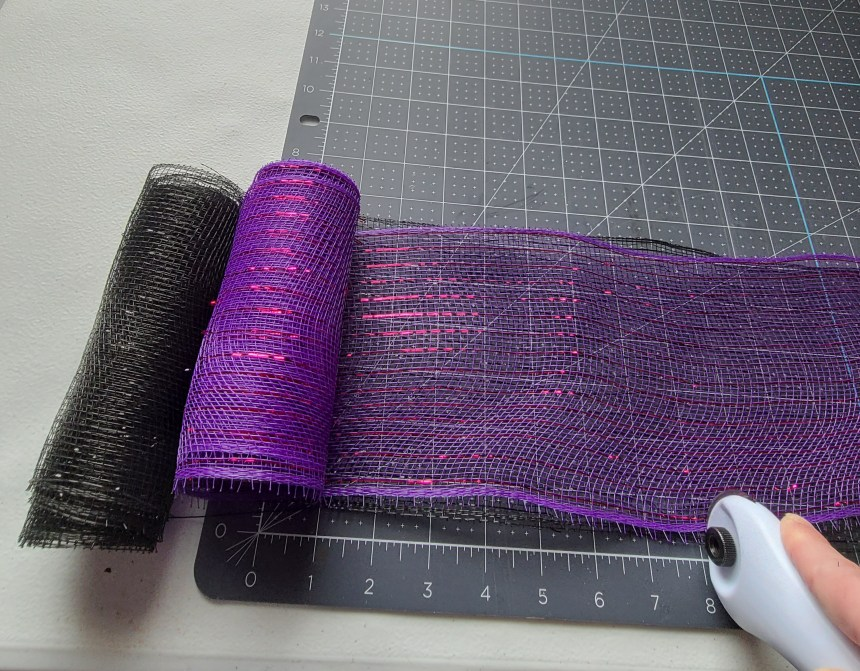 """Cutting purple and black deco mesh on top of a self-healing grid cutting mat into 8"""" pieces with a rotary cutter. These will fill the brim section of the Dollar Tree witch hat."""