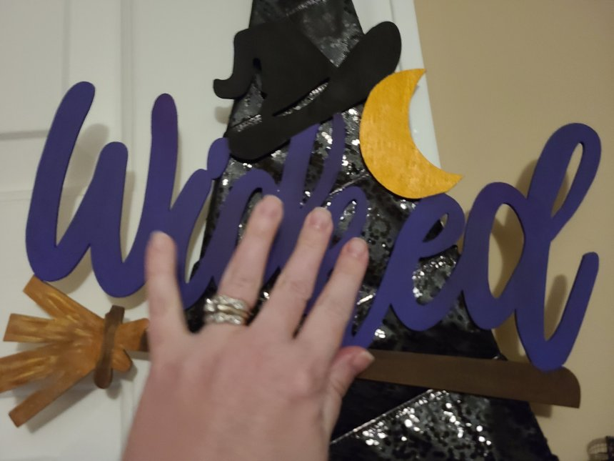 """Hot glue is on the back of the wood """"Wicked"""" sign and my hand is pressing the sign on to the triangle portion of the Dollar Tree witch hat wreath. It is angled a little with the W higher that the end of the word and tip of the broom handle."""