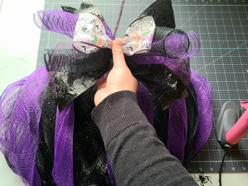 Adding the bow to the middle deco mesh piece on the Halloween pumpkin wreath.