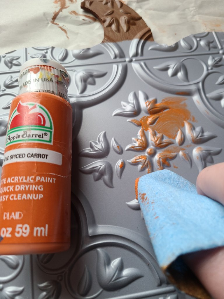 Thick blue paper towels made for automotive being used to apply orange acrylic paint to the tile on the fall pumpkin sign in circular patterns.