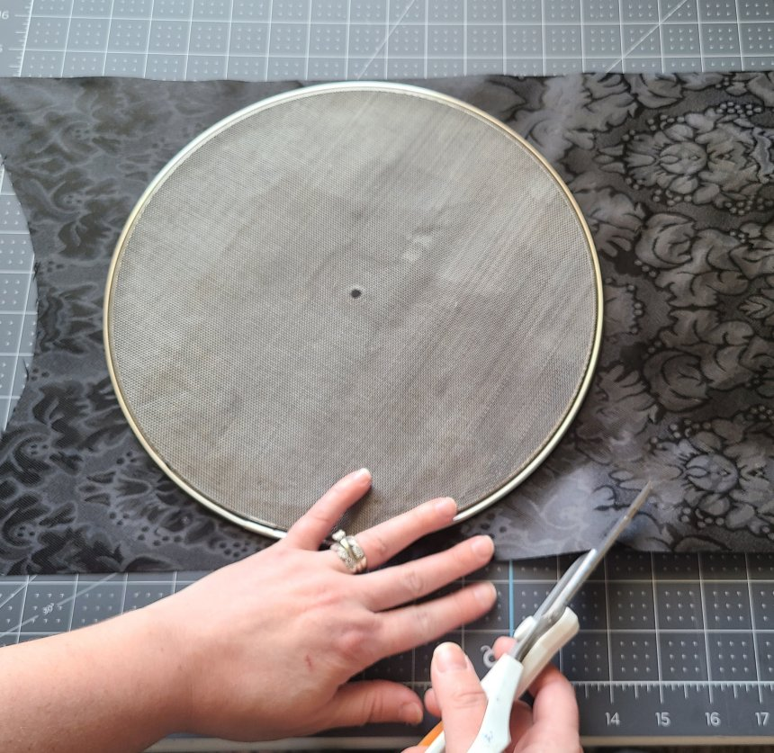"""Cutting fabric for a Halloween splatter screen pumpkin. The screen is laid in the middle of a black table runner in the middle height-wise, then leaving about 3"""" on the sides, scissors are being used to cut around the screen."""