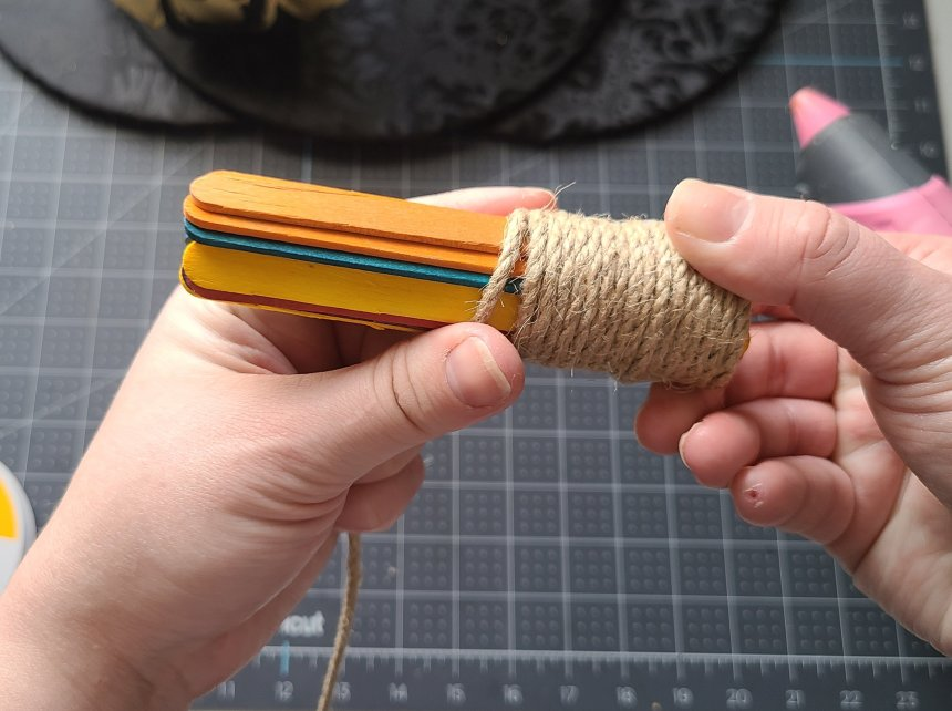 Wrapping 3mm rope around popsicle sticks that will be the stem on the Halloween splatter screen pumpkin.