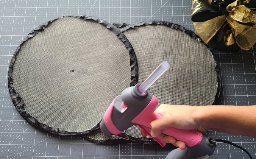 Adding hot glue to the back of the Halloween splatter screen pumpkin in the upper middle section.