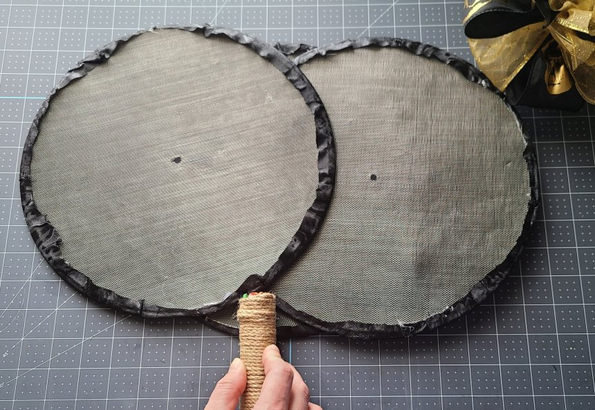 Placing the stem on top of the hot glue on the back of the Halloween splatter screen pumpkin.
