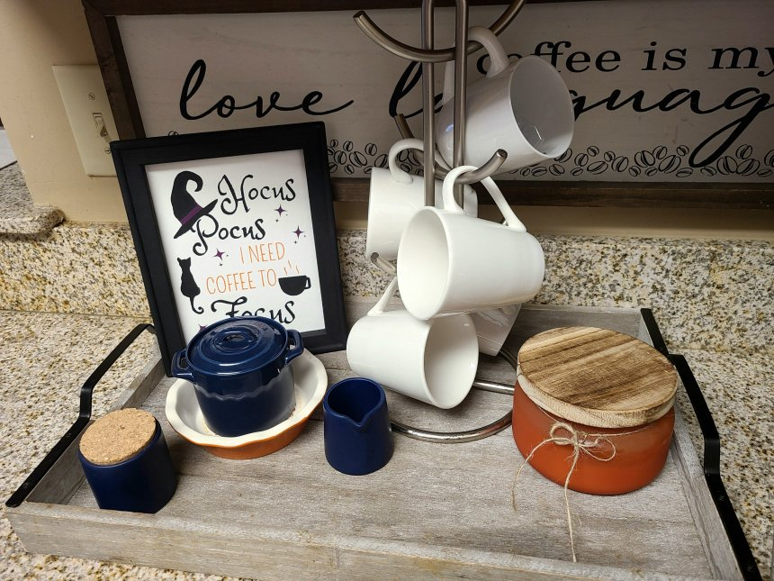 Hocus Pocus sign set in a tray full of coffee cups, sugar container, milk cup, and orange pumpkin candle.
