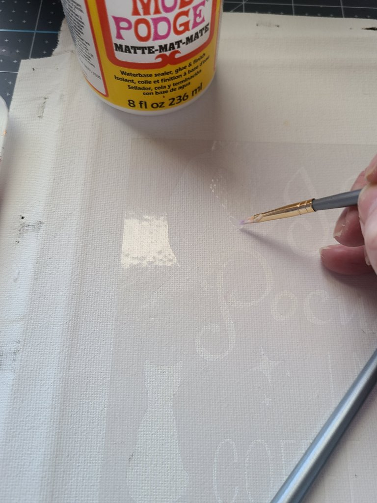 Brushing matte Mod Podges along the edges of the letters and shapes of the stencil on canvas.