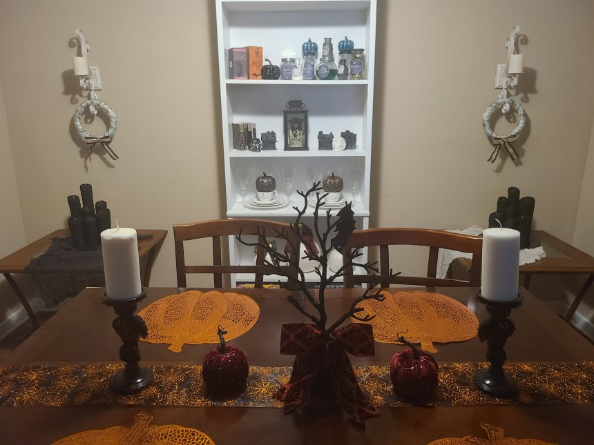 My dining room decorated for Halloween with one Halloween candle centerpiece on each of the two side tables next to the white bookcase.