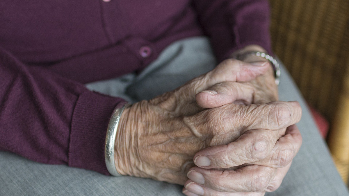 The loneliness epidemic is emphasised by the hands of an old person. Many old people live alone and isolated.