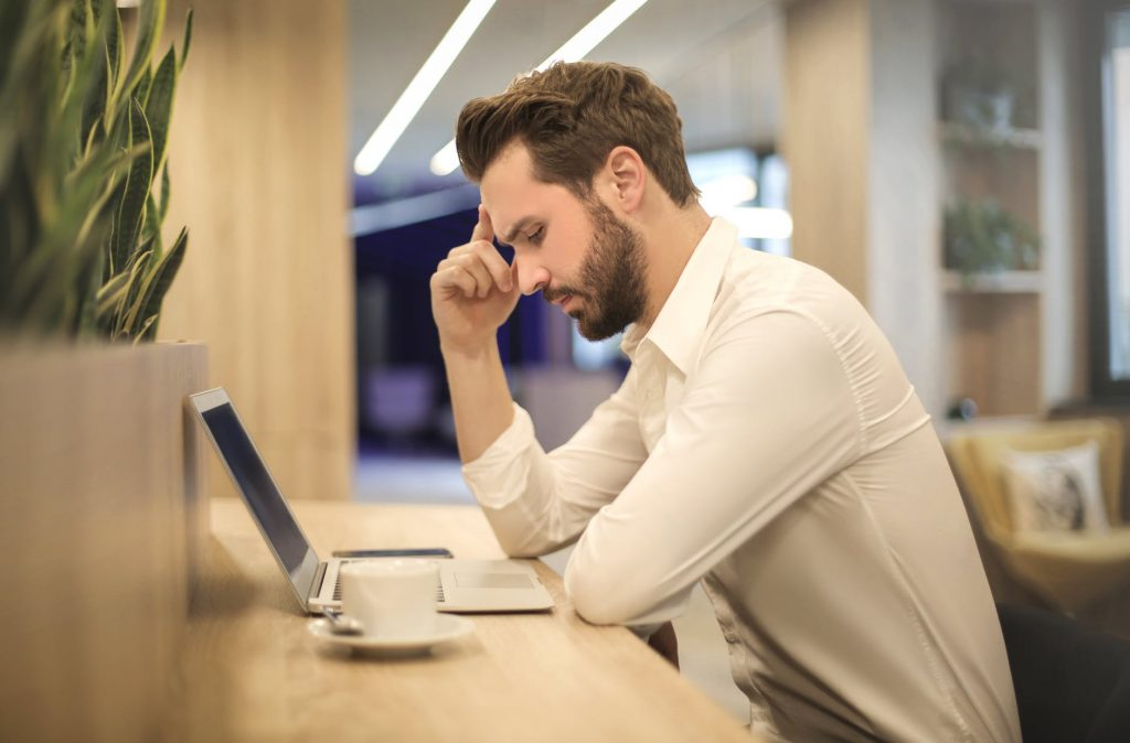 Image of man looking stressed at work, staring at his computer