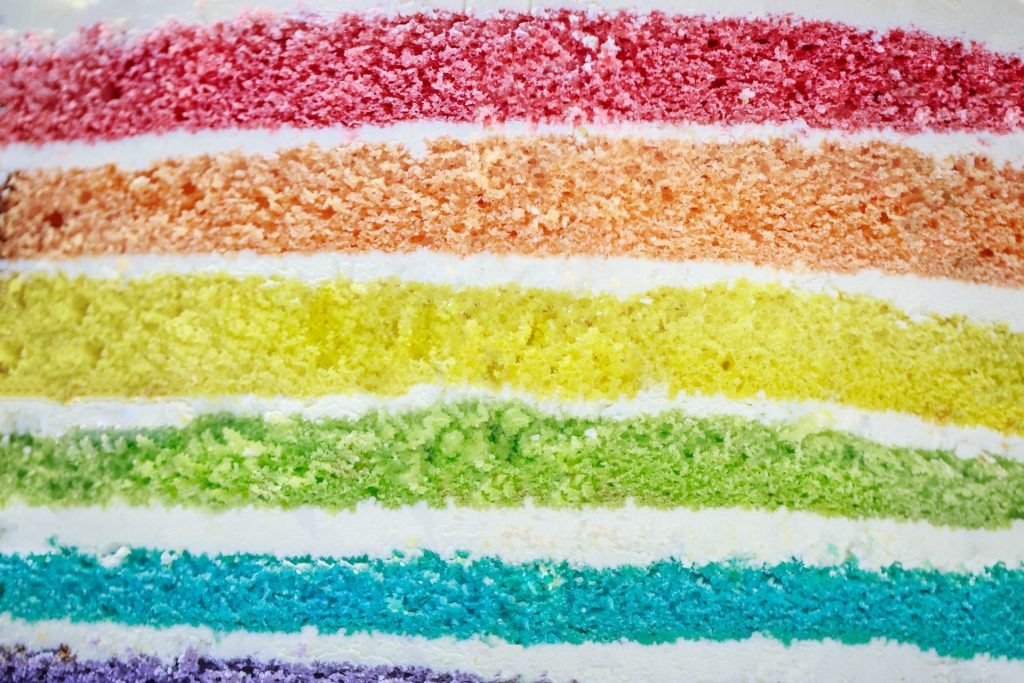 Image of close up of a slice of rainbow cake