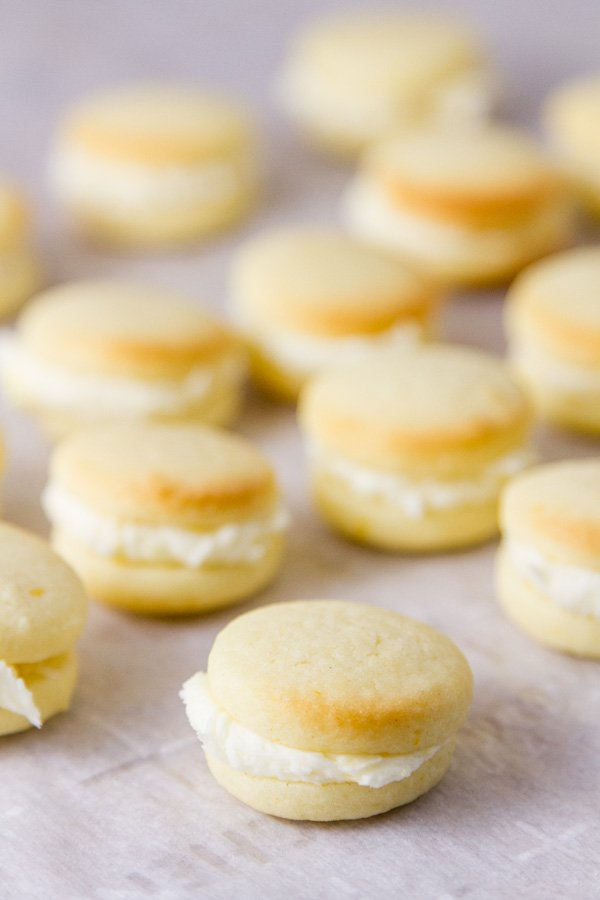 small bite sized sandwich cookies on a piece of white parchment paper