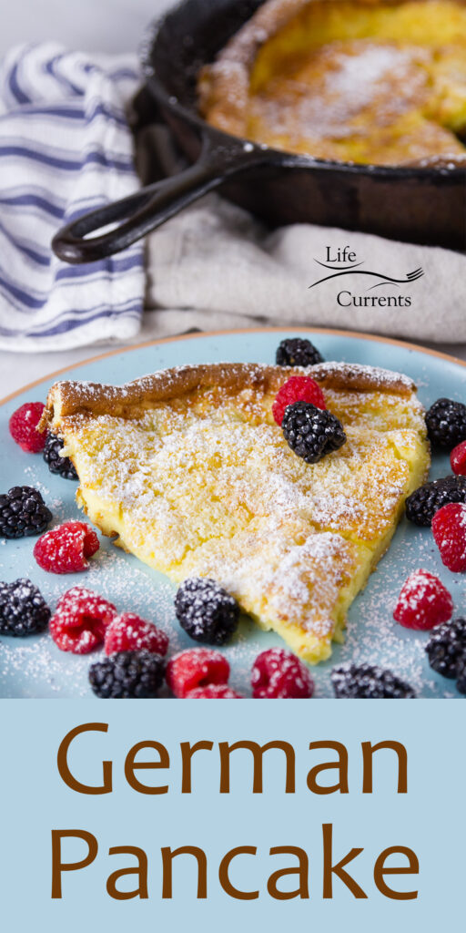 a slice of German Pancake with raspberries and blackberries on a blue plate and the pan of pancake in the background