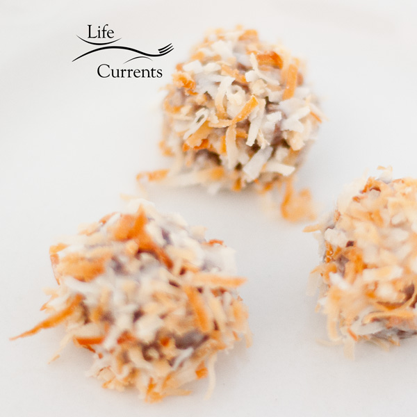 Coconut and white icing top the Boozy Black Forest Rum Balls to look like little snow balls