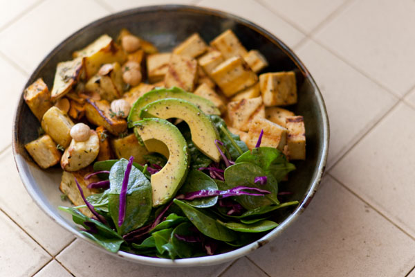 Autumnal Salad Salt & Pepper Seared Tofu, Thyme Roasted Sweet Potatoes with Marcona Almonds, and Avocados served on a bed of Spinach and Red Cabbage