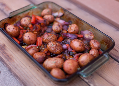 potatoes, carrots, red onions in a baking dish with herbs and sauce