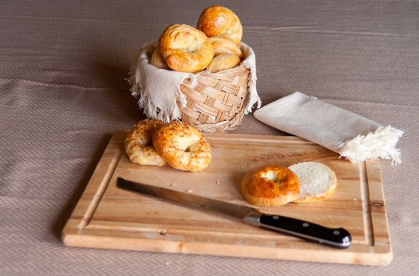 Homemade Bagels in a basket with a cutting board and bread knife