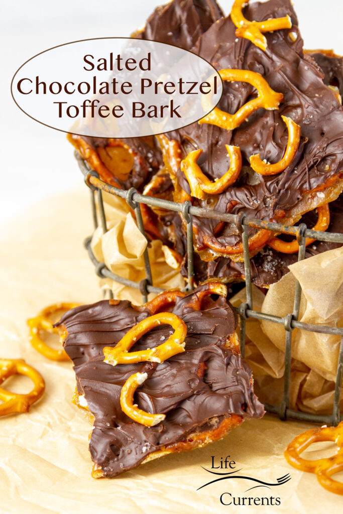 pieces of Salted Chocolate Pretzel Toffee Bark in a wire container with one piece in front and some broken pretzels around.