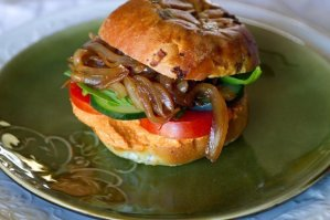 Roasted red pepper hummus sandwich with tomatoes, cucumbers, and caramalized onions. A Veggie vegetarian, vegan delight!