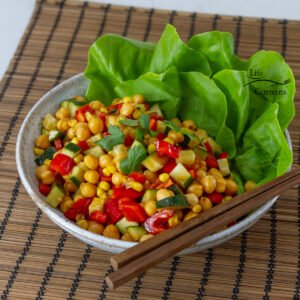 square crop of Asian inspired garbanzo bean salad in a white bowl with lettuce leaves and chopsticks on a brown mat.