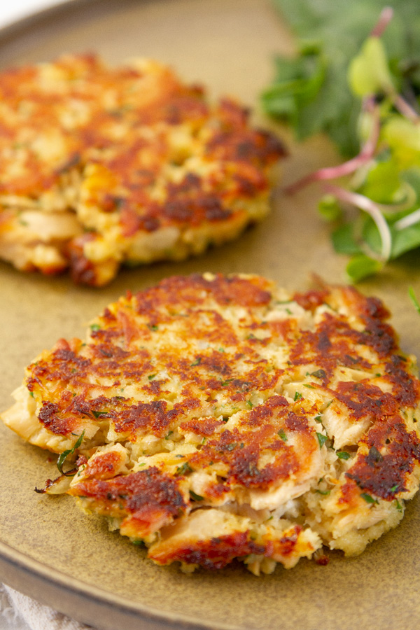 cooked tuna patties on a plate with greens in the background