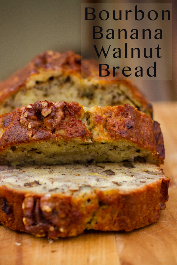 Bourbon Banana Walnut Bread sliced on a wooden cutting board with the title