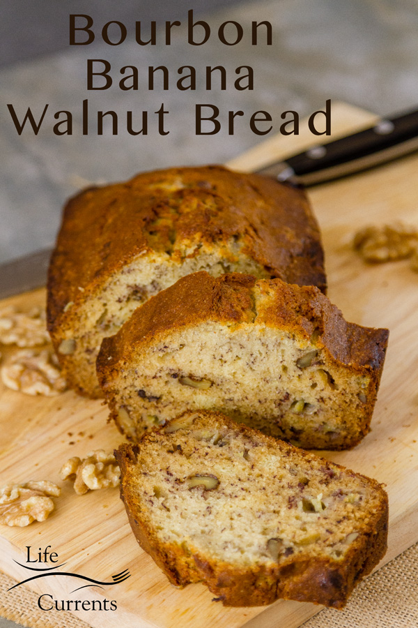 Bourbon Banana Walnut Bread two slices in front of the loaf, a bread knife behind on a wooden cutting board with some walnuts around