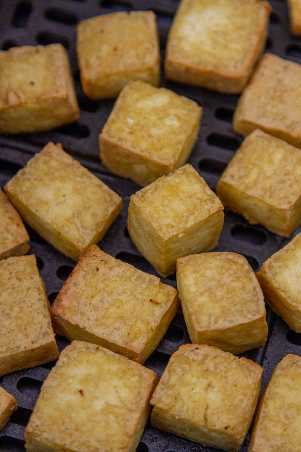 cubes of tofu in the basket of an air fryer