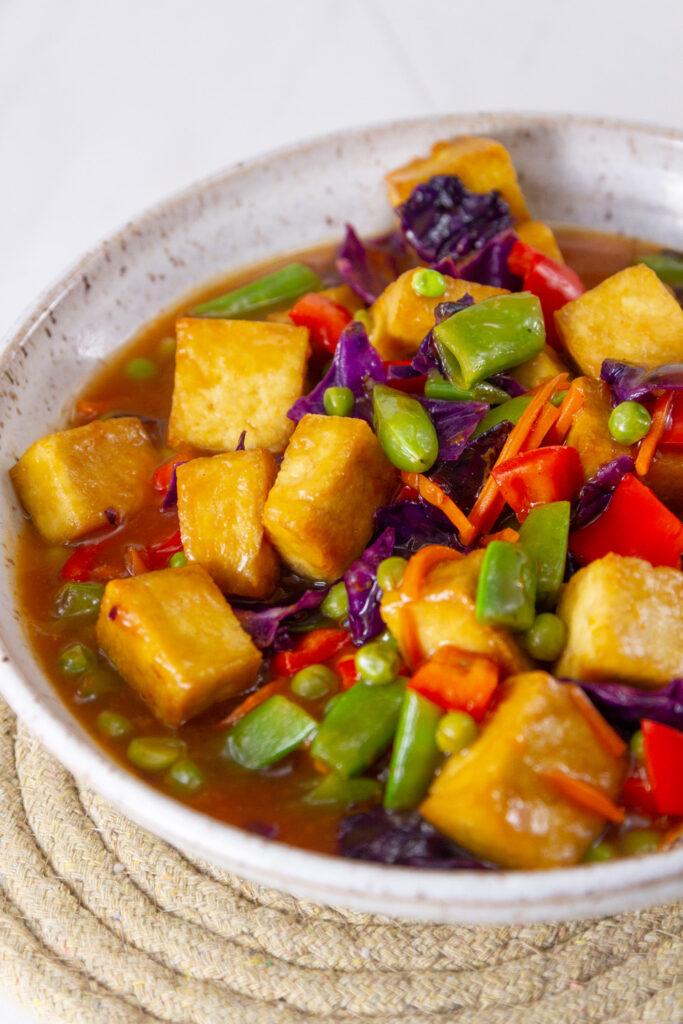 tofu, veggies, and sauce in a white bowl.
