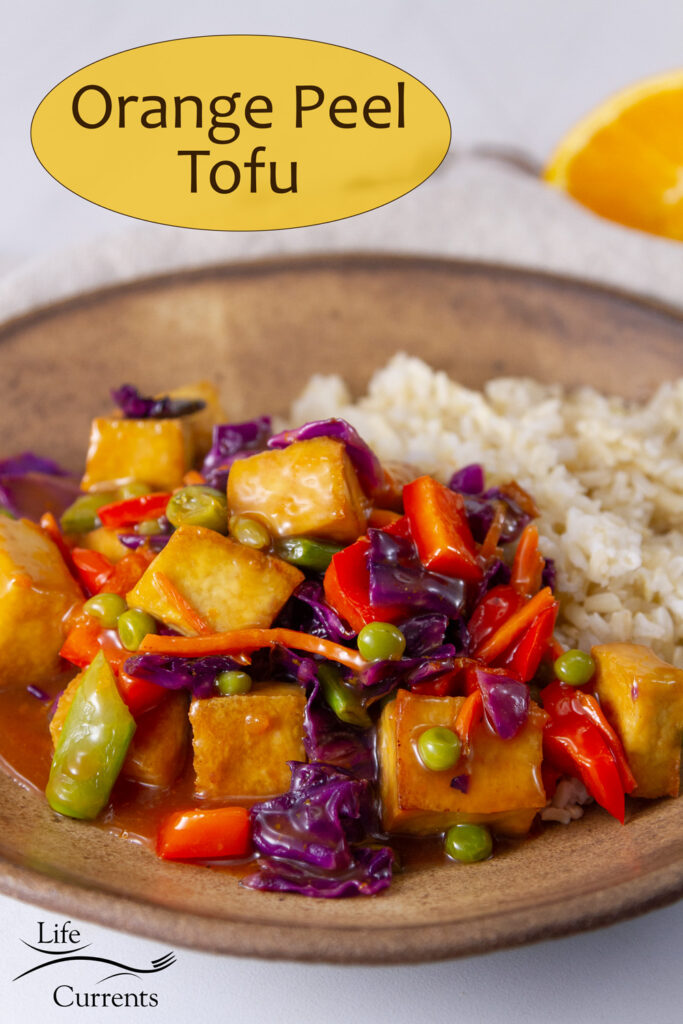 tofu and veggies in orange sauce served with rice on a brown plate with a cut orange in the background.