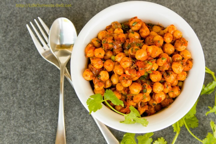 Nacho Roasted Chickpeas in a bowl with a spoon and fork and cilantro leaves