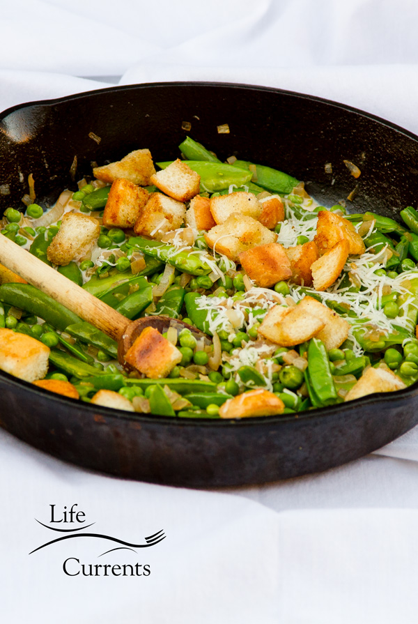 peas and croutons in a cast iron skillet