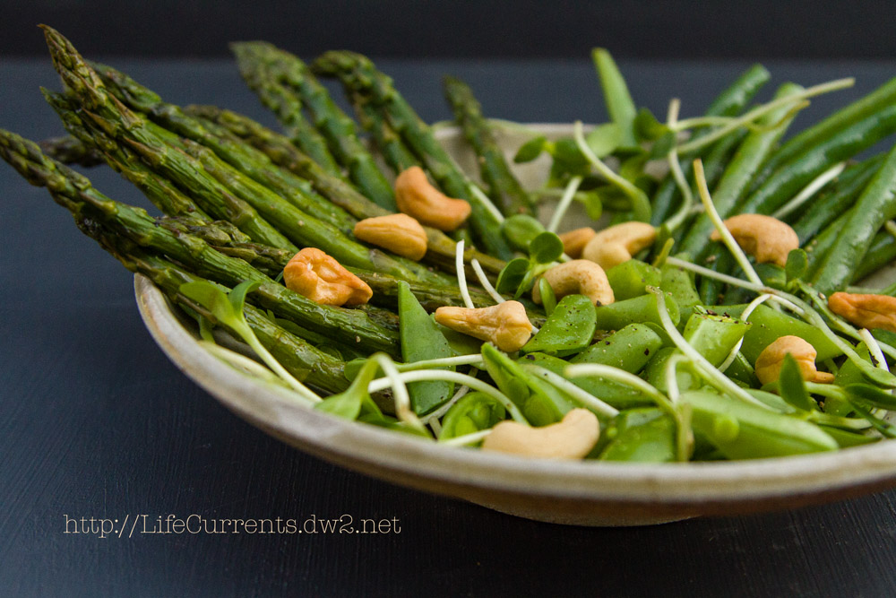 asparagus, green beans, snap peas, cashews, sprouts in a bowl
