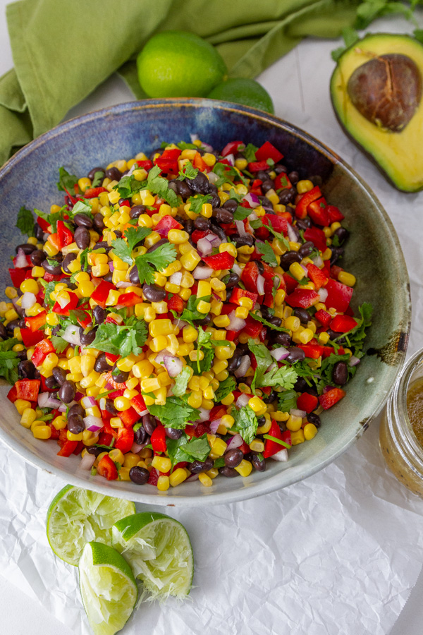 looking down into a bowl of corn salad, served with lime wedges, avocado, and dressing.
