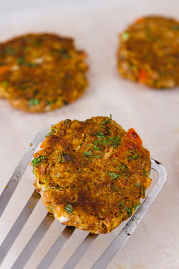 Falafel patties, cooked and one is being picked up on a spatula