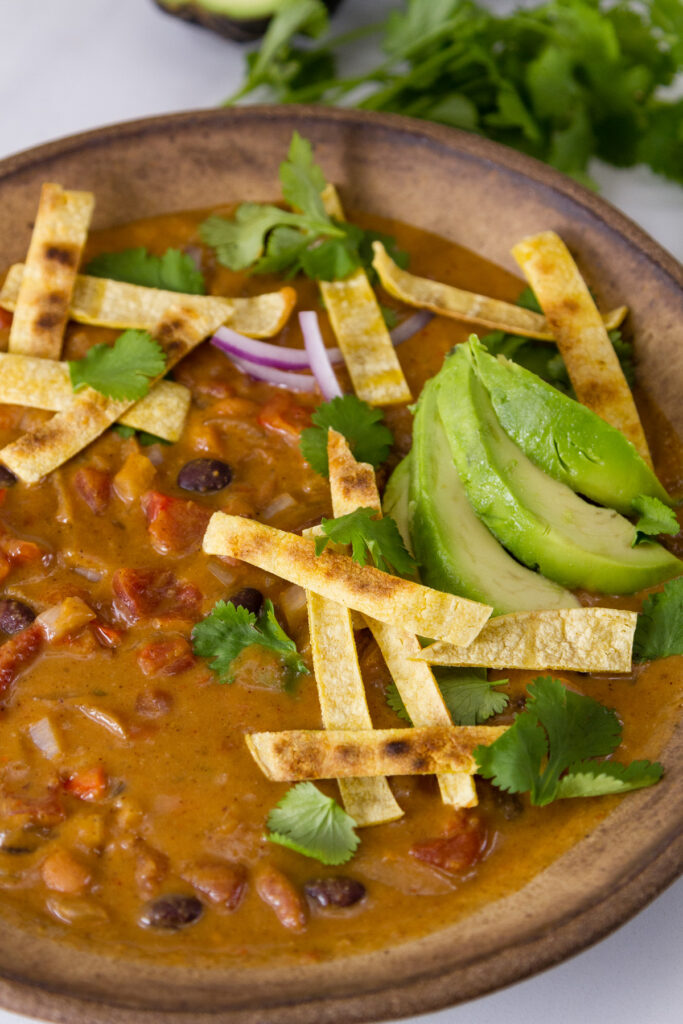 a bowl ful of tortilla soup with lots of garnishes
