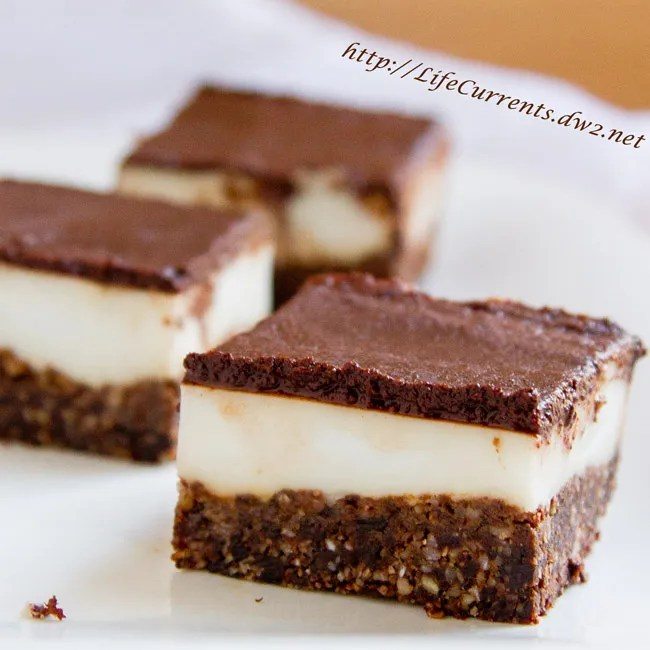 Chocolate Coconut Bites are a healthy nutty coconut crust, topped with a soft (almost custardy) coconut layer, and all capped by a chocolate ganache layer. Yummy! by Life Currents https://lifecurrentsblog.com