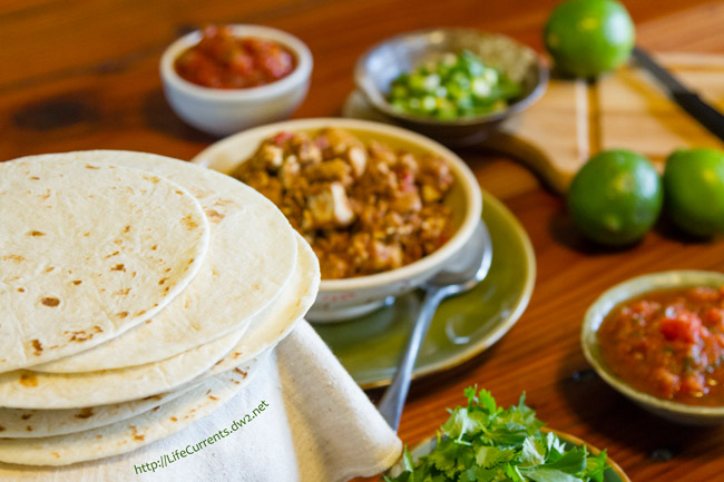 taco bar with tortillas, salsa, all the fillings on the bar