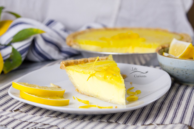 Grandma's Lemon Custard Pie with Lemon Curd Topping horizontal image with lemons in the background and a blue towel