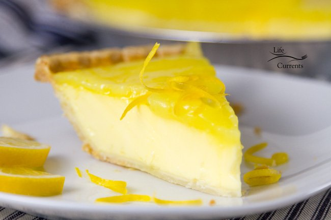A slice of Lemon Custard Pie on a plate with blue ticking in the background