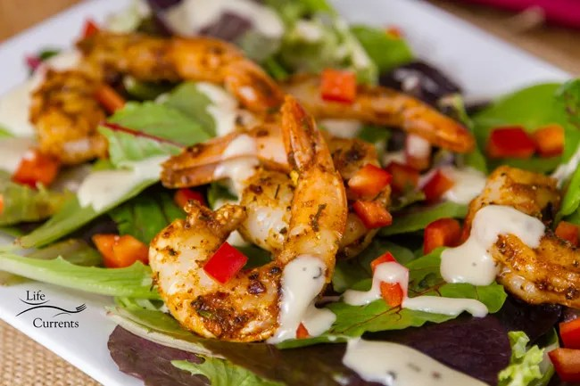Shrimp in Cajun Spice Oil - cooked shrimp tossed in Cajun spices on a bed of mixed greens with red peppers and creamy dressing