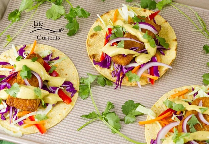 The Best Avocado Sauce served on fish tacos with lots of colorful fresh veggies
