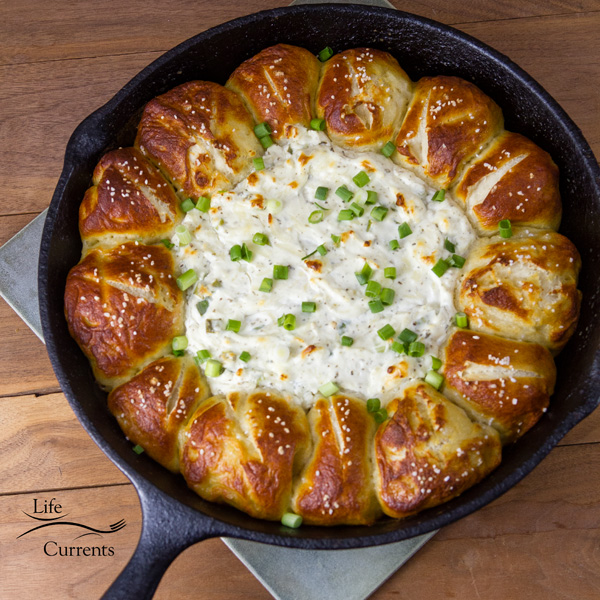 Skillet Pull-Apart Pretzel Buns with Creamy Cheese Dip - Soft delicious pretzel buns surround creamy cheese dip, all baked to a golden gooey perfection in a skillet, making it easy to serve and enjoy right out of the oven!