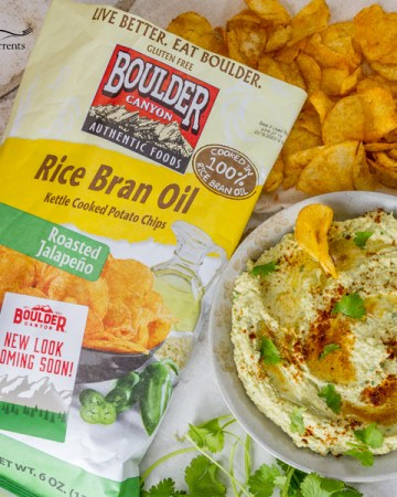 Roasted Jalapeño and Avocado Hummus is a deliciously creamy and healthy hummus with a little kick of roasted jalapeno served with Boulder Canyon chips Roasted Jalapeno Rice Bran Oil Kettle Cooked Potato Chips